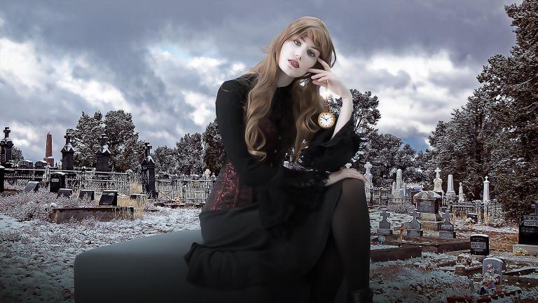 Dark woman with death clock on graveyard