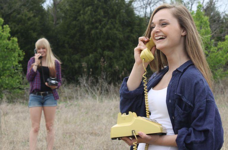 Frauen mit gelbem Telefon am telefonieren