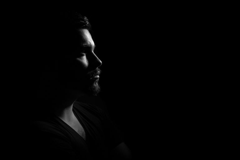 Gloomy profile foto of man - black background
