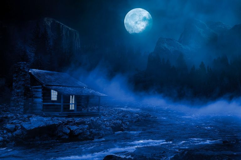 Moon shining during night over a hut near the river