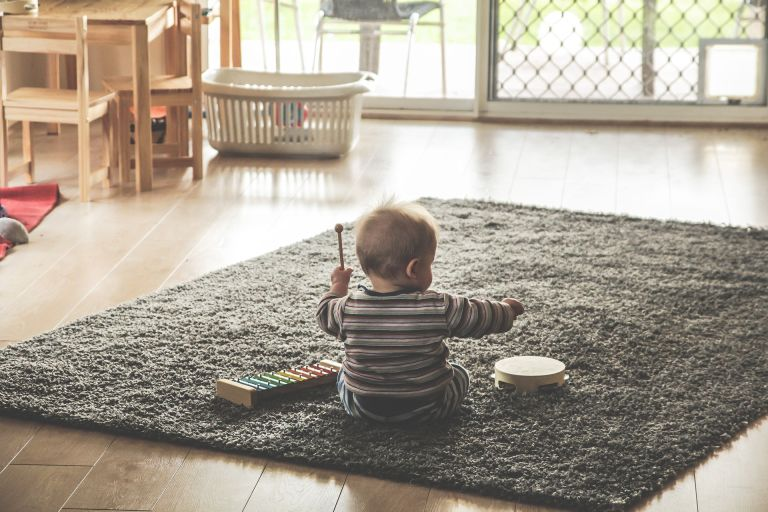 Baby playing xylophone music on carpet