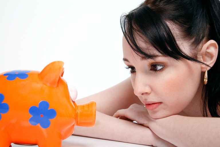 Woman stares at piggy bank: Does she want to save money?