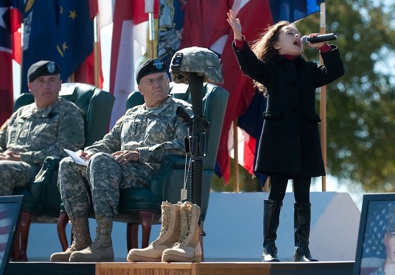 """Rhema Marvanne, 7, sings """"The Prayer"""" during a Remembrance Ceremony at Ft. Hood, TX, Nov. 5, 2010. The ceremony commemorated the lives of 13 people who died in a tragic shooting incident on the installation Nov. 5, 2009. Army photo by D. Myles Cullen (released)"""