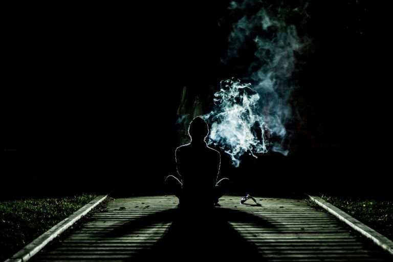 Human meditating and smoking, possibly Marijuana