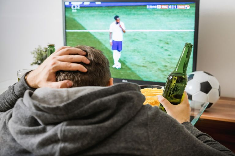 Man drinking in beer in front of TV watching soccer