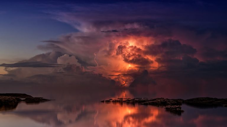 Sunset on mirroring ocean with orange clouds