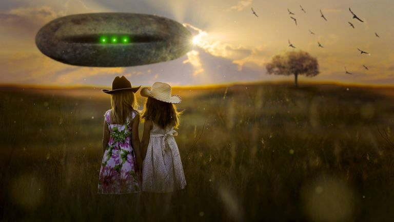 Girls walking in crop circle field with UFO.