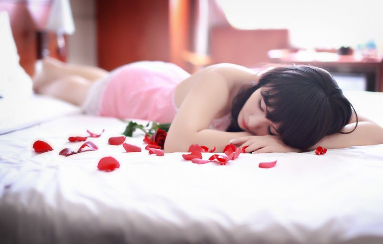 Sad woman in bed with rose petals sleeping