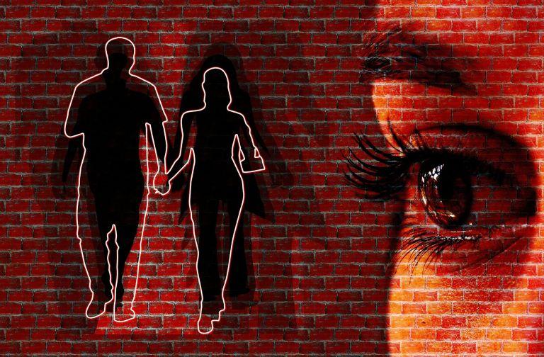 Women's eye and couple as graffiti on wall