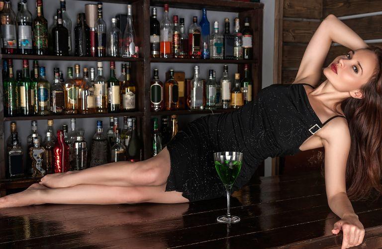 Woman hanging out on a bar, posing, bottlesa