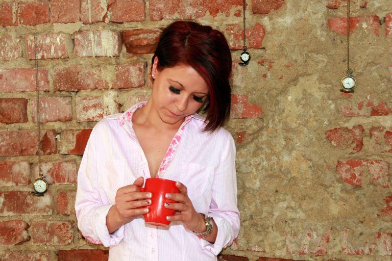 Sad woman drinking cup of coffee