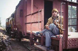 Railway attendant sat on outside of train, Allahabad