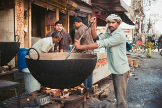 Man stirring large cooking pot in the street