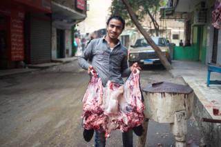 Butcher holding carcass, Cairo
