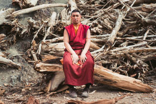 Monk sat on pile of wood