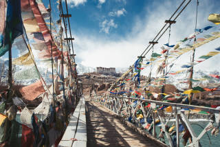 Monastery over a bridge covered in prayer flags