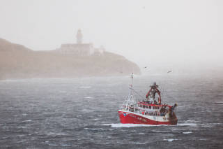 Fishing vessel passing lighthouse in stormy seas