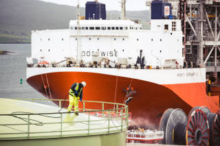 Heavy lift vessel and a worker cleaning a large tank