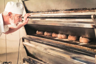 Baker checking bread in oven