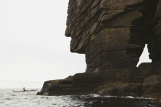 Kayaker next to natural arch, Boddam