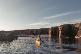 Kayaker below cliffs, Braewick