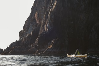 Kayaker below cliffs, Hillswick Ness