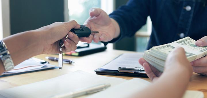dos personas intercambiando dinero y las llaves de un auto