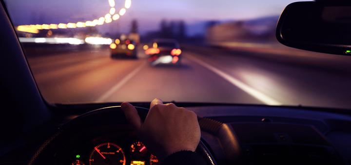 persona manejando de noche por la carretera