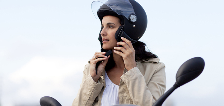 una mujer colocandose el casco de una moto