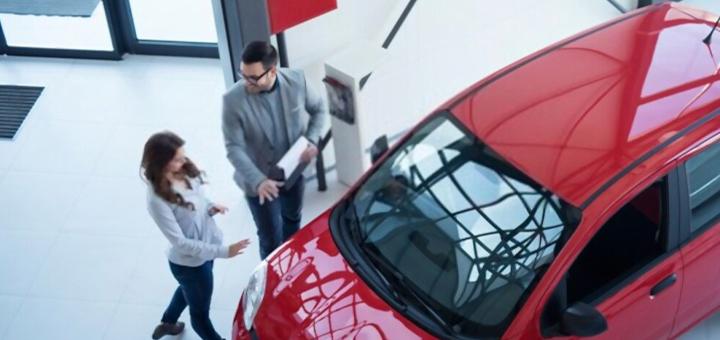 dos personas frente a un auto de color rojo