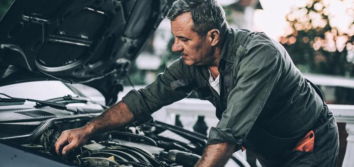 señor arreglando un motor