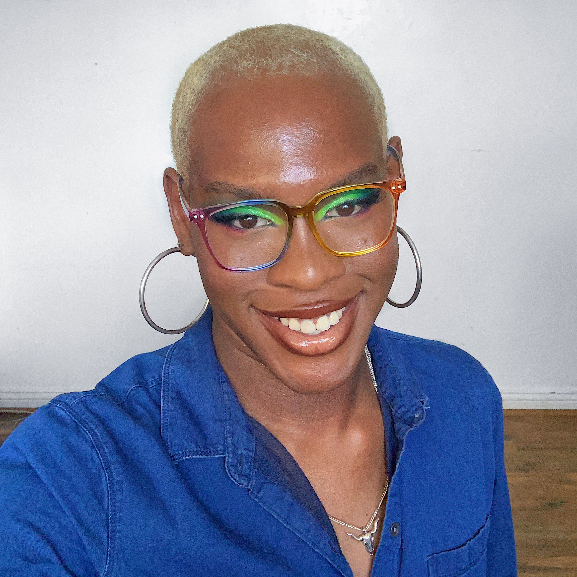 A person wearing rainbow-colored eyeglasses