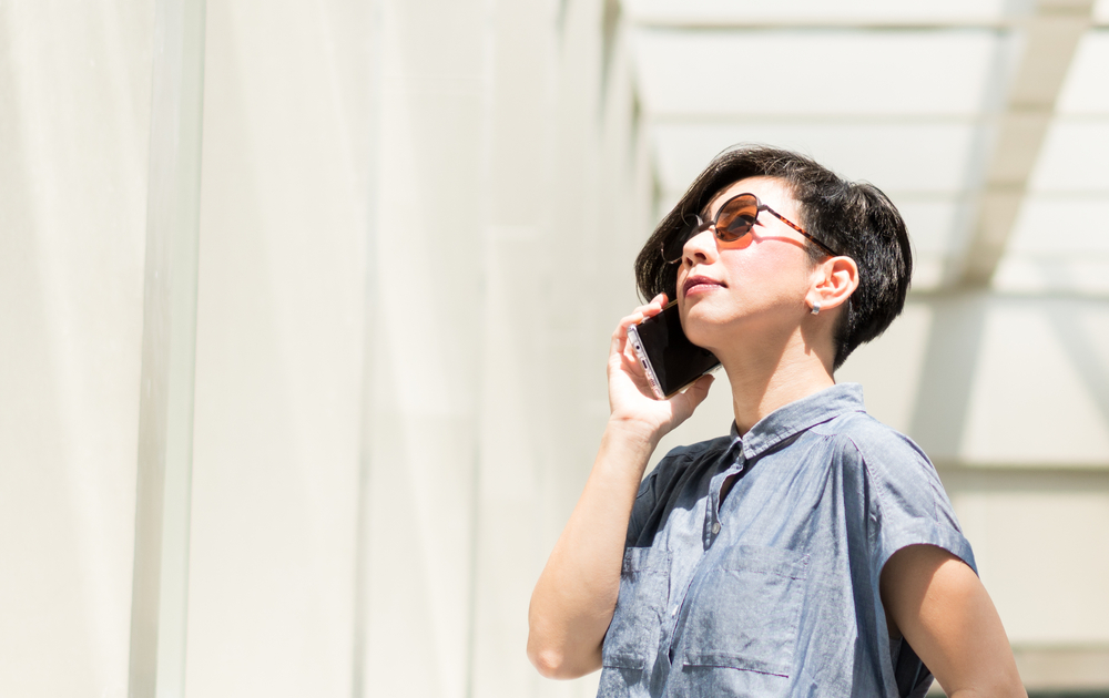 A woman wearing sunglasses and talking on the phone