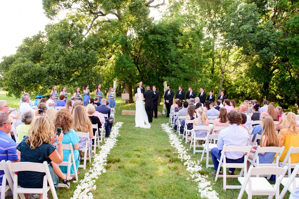 summer outdoor wedding ceremony with trees in background