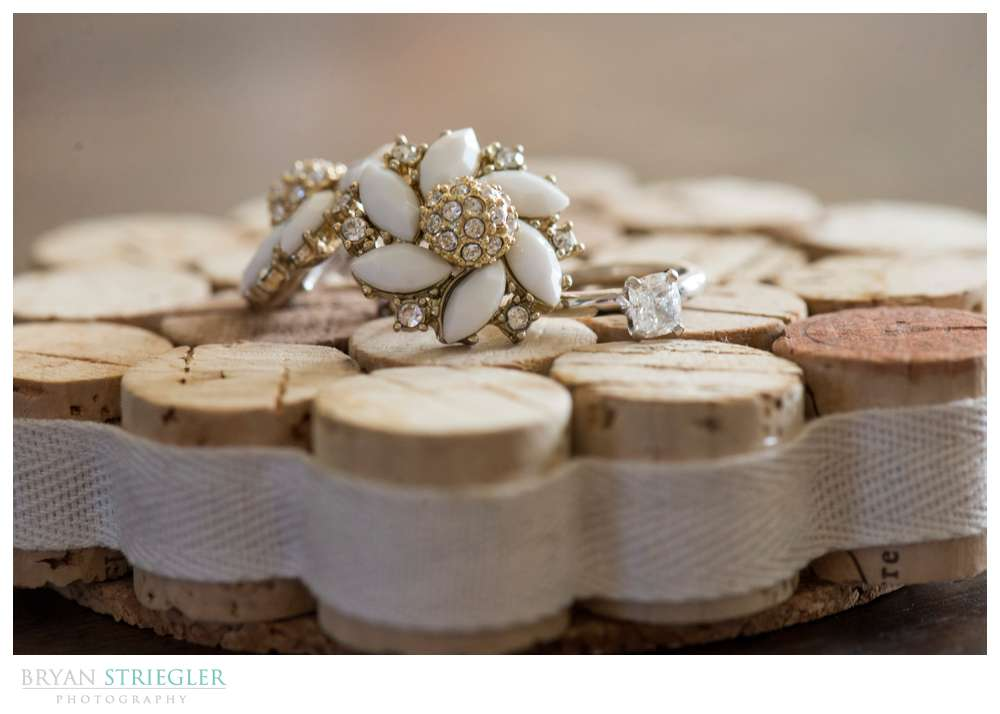 earrings and engagement ring together on wine corks