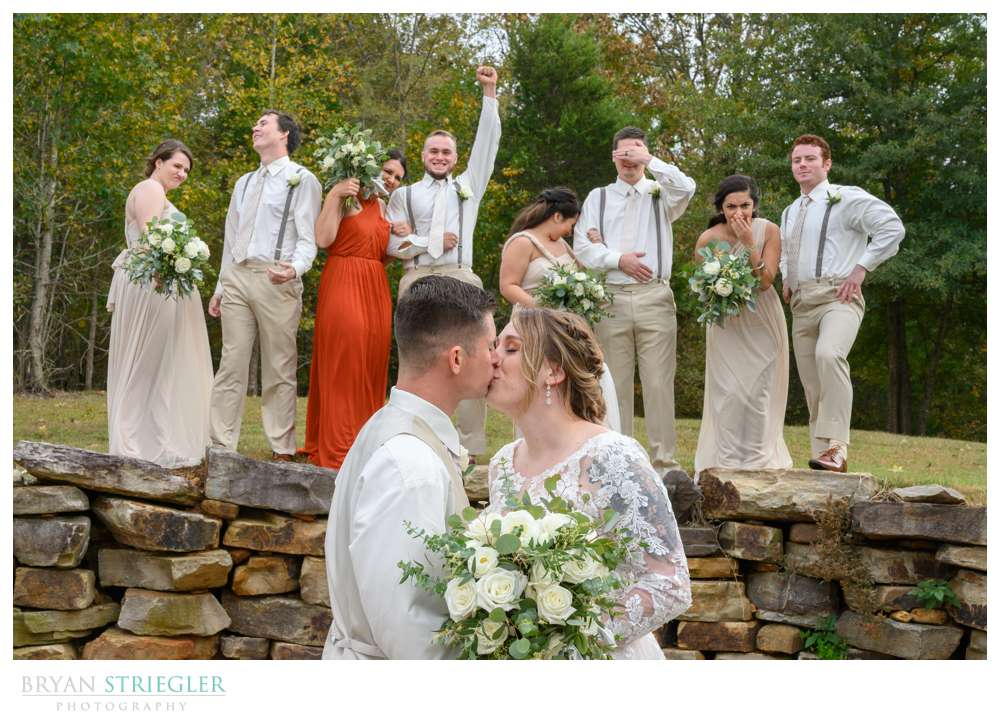wedding party reacting to kissing couple