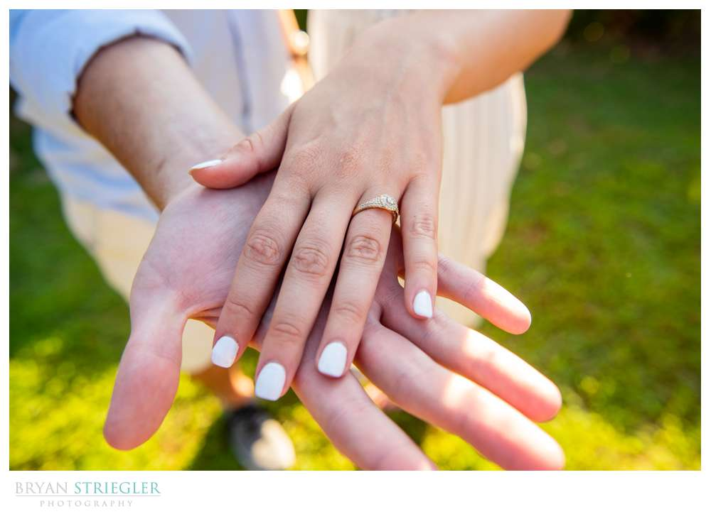 couples hands together with engagement ring