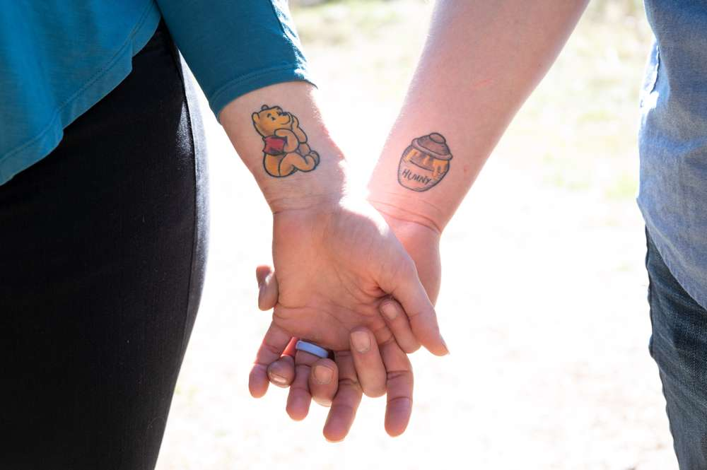 Couple with Winnie the Pooh tattoos