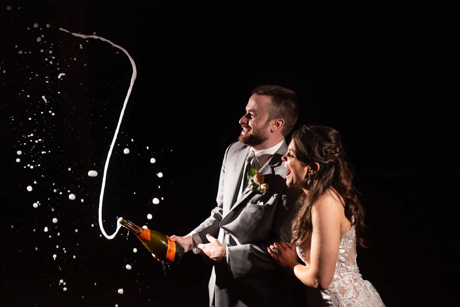 popping champagne at wedding