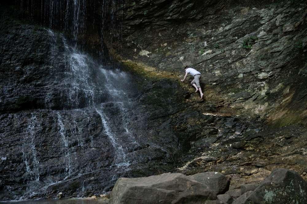 guy climbing waterfall