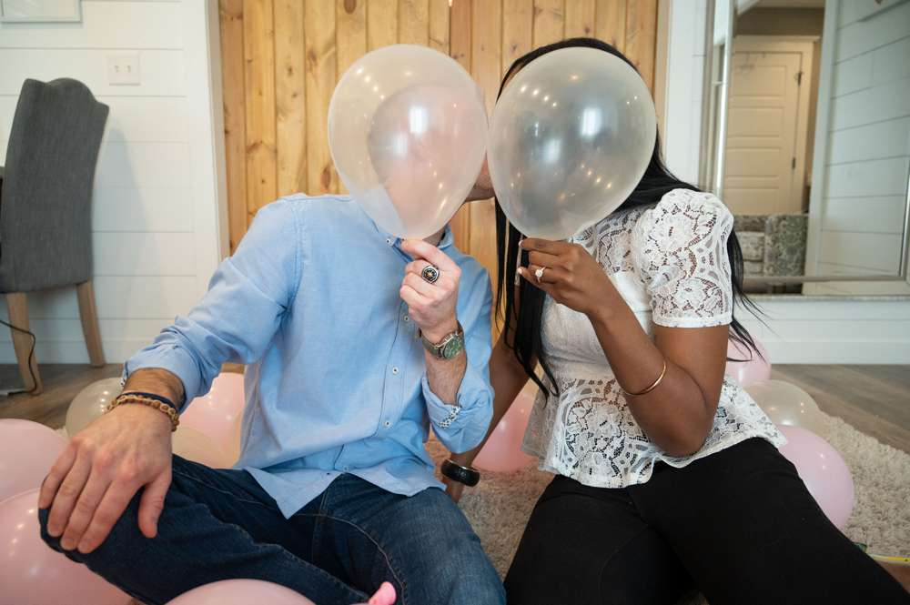engagement couple hiding behind balloons