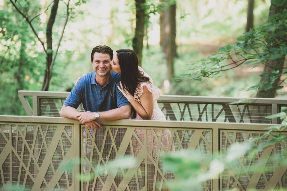 couple leaning on bridge