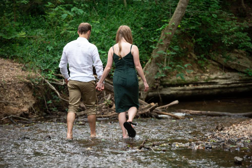 engaged couple walking in a creek