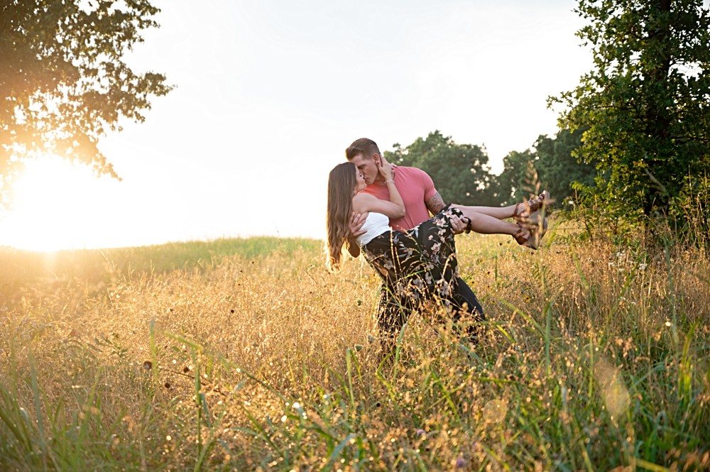 guy carrying girl through field with sunset