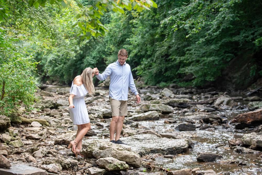 couple crossing a creek