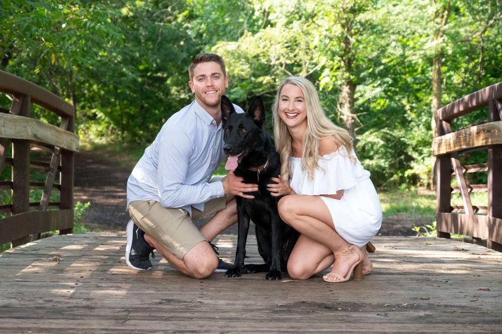couple with dog on bridge