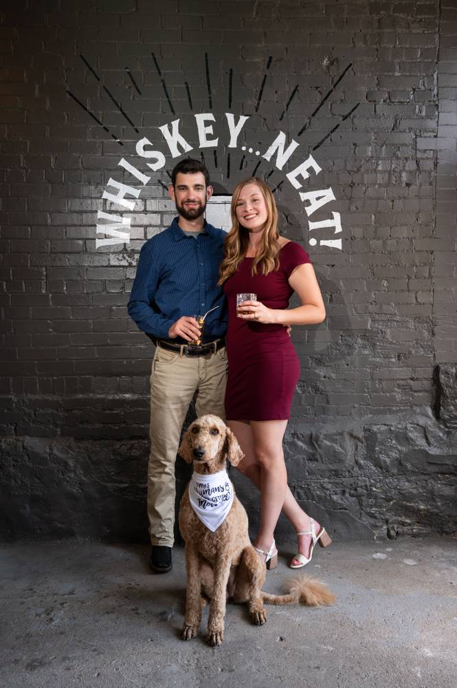 couple standing by logo of whiskey bar