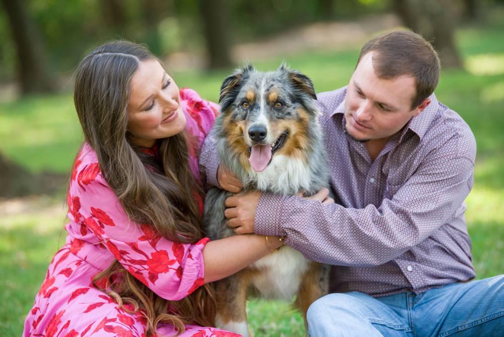 engaged couple hugging dog
