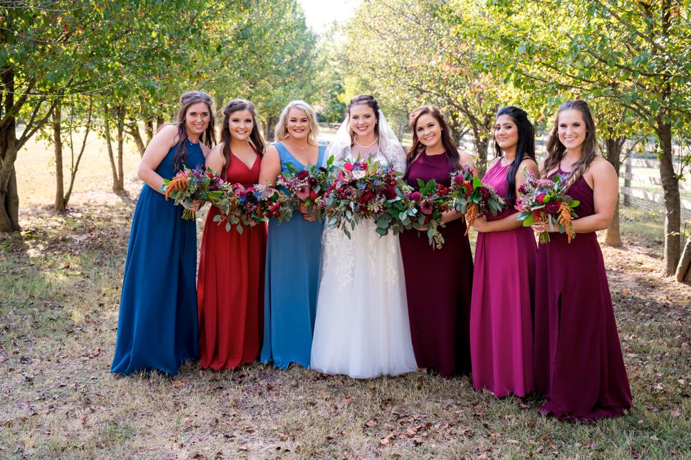 bride and bridesmaids with different color dresses