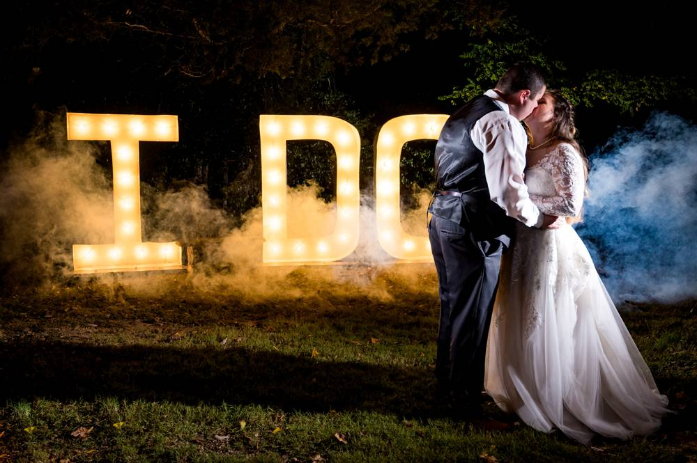 wedding photo at night with light up sign and smoke